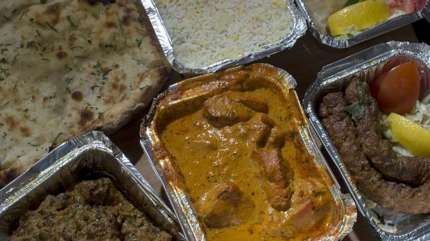 Lamb and chicken curries surrounded by Indian take away food