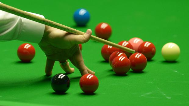 A snooker player plays a shot during a match