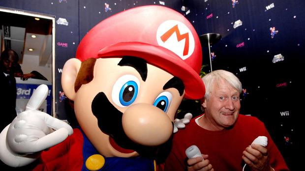 The voice of Super Mario poses with the game character