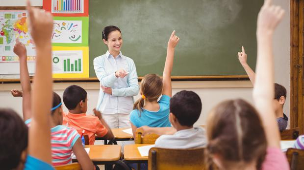 Teaching asking a question in a classroom (Wavebreakmedia/Getty Images)