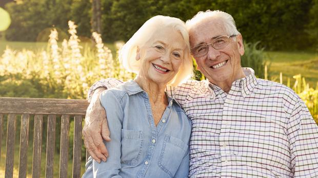 An elderly couple sitting on a garden bench – (monkeybusinessimages/Getty Images)