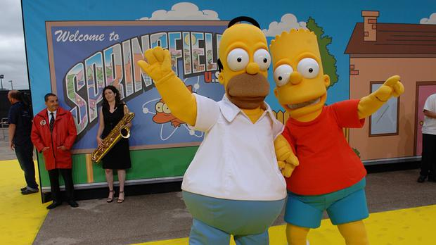 People dressed as Homer (left) and Bart Simpson arrive for the UK Premiere of The Simpsons Movie, at the Vue Cinema, The O2, Peninsula Square, London – (Joel Ryan/PA)