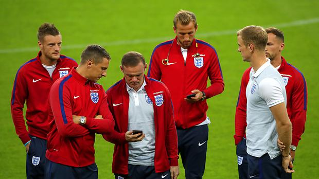 England players check their phones while walking around a football pitch – (Nick Potts/PA)