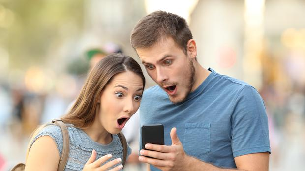 A couple react with shock to something on a mobile phone (AntonioGuillem/Getty Images)