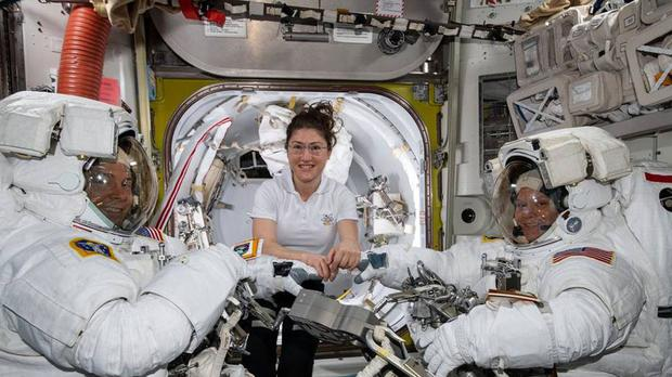 Nasa astronaut Christina Koch, centre, assists fellow astronauts Nick Hague, left, and Anne McClain (Nasa/PA)