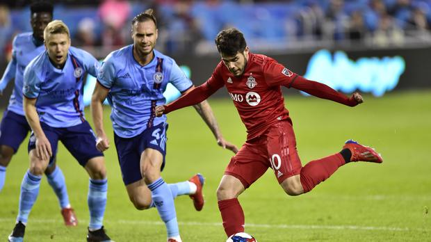 Toronto FC's Alejandro Pozuelo, right, kicks toward the goal against New York City FC during first-half MLS soccer action in Toronto, Friday, March 29, 2019. (Frank Gunn/The Canadian Press via AP)