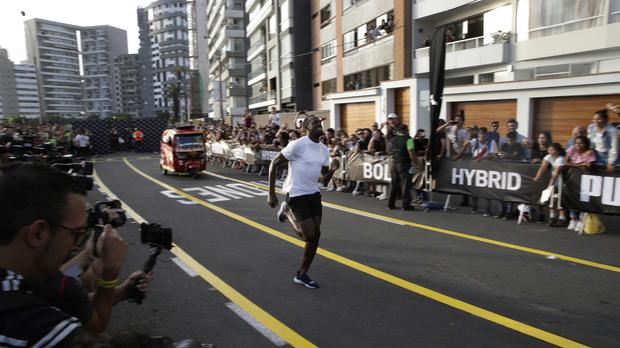 Usain Bolt has beaten a motorcycle taxi in a race in Peru (Martin Mejia/AP)