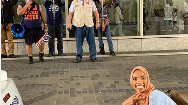 A photo of Shaymaa Ismaa'eel smiling in front of a group of anti-Islam protesters in Washington, DC (Shaymaa Ismaa'eel)