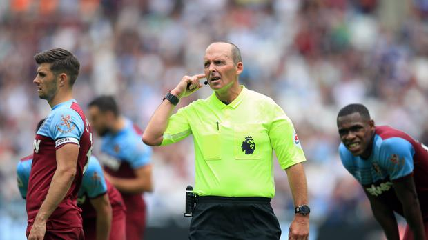 Referee Mike Dean ahead of the VAR decision for Manchester City's Sergio Aguero's penalty during the Premier League match at London Stadium (PA)