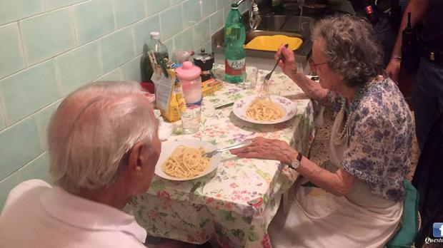Two police officers serve pasta to an elderly couple in Rome (AP)