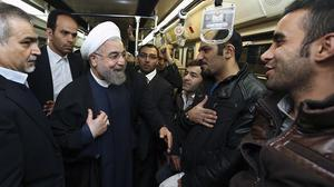 Iran's president Hassan Rouhani, centre, talks to people on board the Tehran metro system (AP/Iranian Presidency Office, Mohammad Berno)