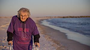Ruby Holt, 100, walks on the beach for the first time in her life (AP)