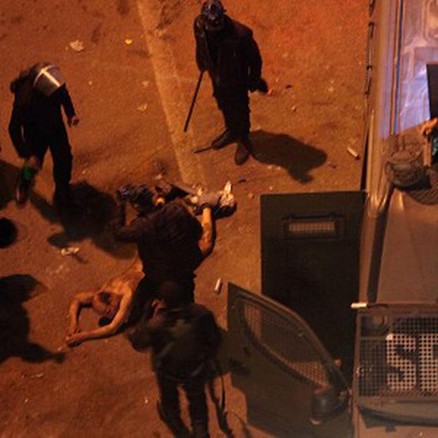 Egyptian riot police beat a man before dragging him into a police van in Cairo (AP/Khalil Hamra)