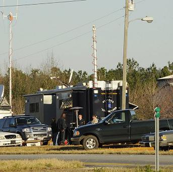 Police and Emergency personnel remain on site at the property of Jimmy Lee Sykes Sunday Feb. 3, 2013 just off Highway 231 north of Dothan, Ala. Suspect Jimmy Lee Dykes has been holed up in a bunker on his property with the a 5-year-old child since the late afternoon shooting on Tuesday, Jan. 29, 2013. Signs have posted posted all over Midland City in support of the 5 year old boy being held hostage with many placed around Midland City Elementary school. Area churches offered prayer for the boy, his family and law enforcement officers trying to bring the situation to a peaceful end. (AP Photo/AL.com, Joe Songer)
