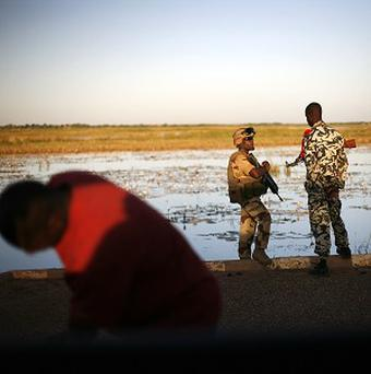 A French soldier speaks with a Malian counterpart on the banks of the Niger river outside Gao (AP)