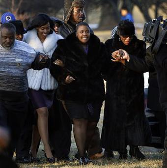 Cleopatra Pendleton, centre, is escorted to the gravesite of her daughter Hadiya (AP)