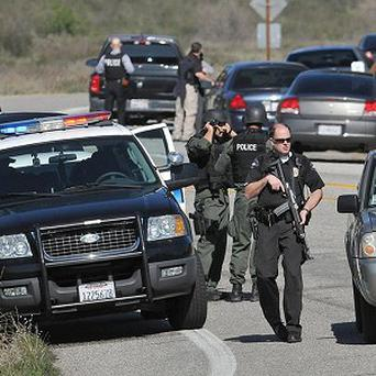 Police officers man a blockade near the entrance to the San Bernardino National Forest in southern California (AP/The Sun, Gabriel Luis Acosta)