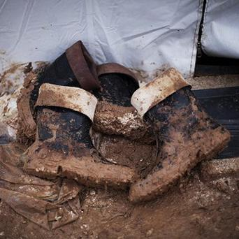 Muddy boots belonging to Syrian refugees are seen at the entrance of a tent in a refugee camp near Azaz, north of Aleppo province, Syria (AP)