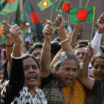Bangladeshis wave flags and shout slogans demanding death to Islamic political party leaders who are on trial for alleged war crimes during the country's 1971 independence war, in Dhaka, Bangladesh, Saturday, Feb. 23, 2013. Eight top leaders of Jamaat-e-Islami, the country's largest Islamic party, are being tried on charges of mass killings, rapes and arson allegedly committed during Bangladesh's nine-month war of separation from Pakistan. (AP Photo/Pavel Rahman)