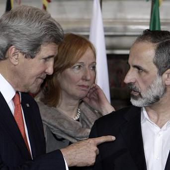 US Secretary of State John Kerry, left, talks to Syrian opposition coalition leader Mouaz al-Khatib, during the Rome conference (AP)