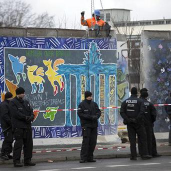 German police officers protect a part of the Berlin Wall (AP)