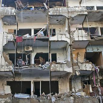 Pakistanis check the damage in an apartment block damaged by a car bombing in Karachi (AP)