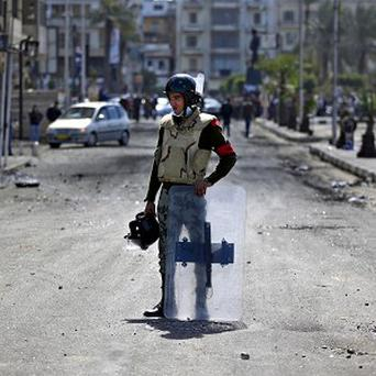 An Egyptian army soldier stands guard during clashes between protesters and riot police near the state security building in Port Said (AP)