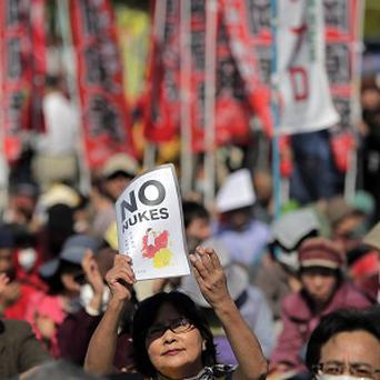 A protester holds aloft an anti-nuclear power plant sign as they stage a rally at a park in Tokyo (AP)