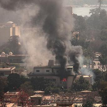Smoke and fire rises from the Egyptian Football Federation after protesters set fires following a court verdict (AP)