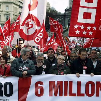 Union leaders carry a banner reading, 'unemployment, six million' during a protest against austerity measures in Madrid, Spain. (AP)