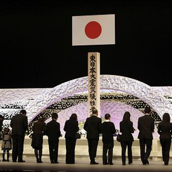 Relatives of earthquake and tsunami victims offer chrysanthemums during the national memorial service in Tokyo (AP)