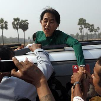 Burmese opposition leader Aung San Suu Kyi greets villagers as she visits Sae-Tae village near the Letpadaung copper mine project (AP)