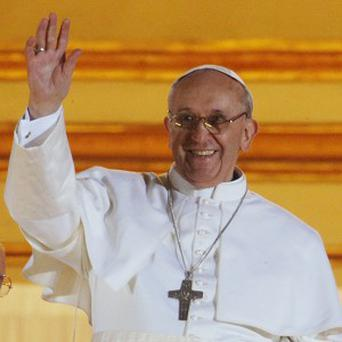 Pope Francis waves from the central balcony of St Peter's Basilica at the Vatican (AP)
