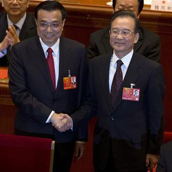 Chinese Premier Li Keqiang, left, shakes hands with former Chinese Premier Wen Jiabao