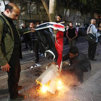 Egyptian protesters burn the Libyan flag during a protest in front of the Libyan embassy, in Cairo, Egypt (AP)