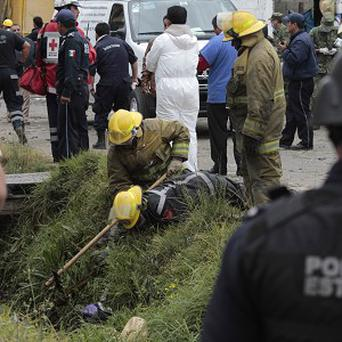 Emergency workers search for human remains in a ditch after a truck loaded with fireworks exploded during a religious procession (AP)