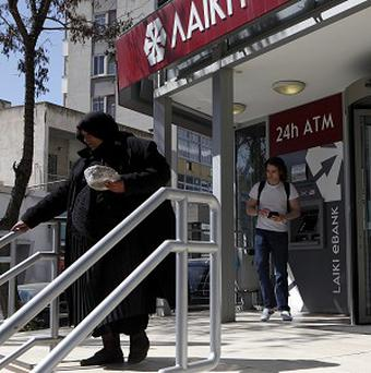 An elderly woman leaves a bank as another man tries an ATM machine in Nicosia, Cyprus (AP)