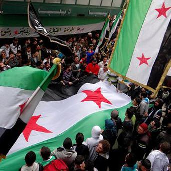 Anti-Syrian regime protesters wave revolutionary flags during a protest in Aleppo (AP/Aleppo Media Center)