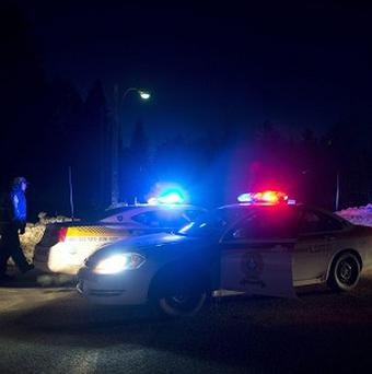 Police vehicles block a road just outside the town of Chertsey, Quebec, during a search for two escaped prisoners (AP)