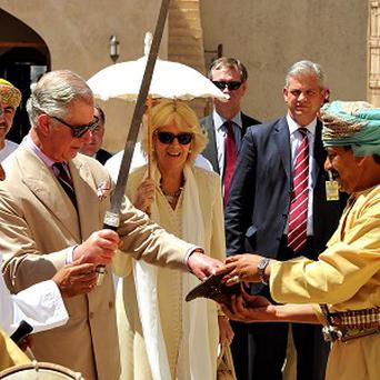 The Prince of Wales is given an Omani sword while he and the Duchess of Cornwall visit the Nizwa Fort on day two of their tour of Oman
