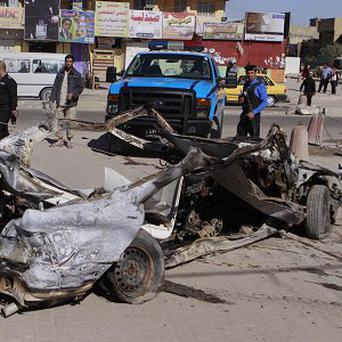 Iraqi security forces inspect the scene of a car bomb attack in the Shia stronghold of Sadr City, Baghdad (AP)