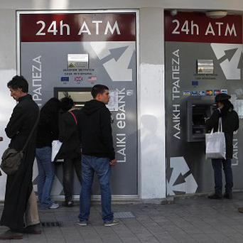 People queue to use cash machines at Laiki Bank in Nicosia, Cyprus (AP)