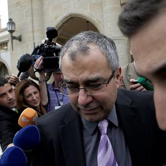 Cyprus' Central Bank chief Panicos Demetriades leaves after a meeting in the presidential palace in the capital Nicosia (AP)