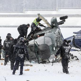 Rescue workers examine two crashed helicopters near the Olympic Stadium in Berlin (AP)
