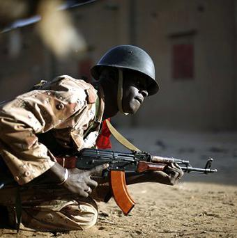 A Malian soldier takes cover behind a truck during exchanges of fire with jihadists in Gao, northern Mali (AP/Jerome Delay)