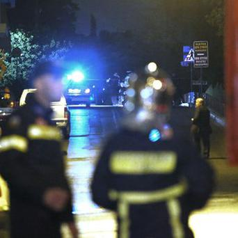 Police set up a cordon after a bomb exploded at the home of a Greek shipowner, opposite the Acropolis in central Athens (AP)