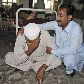 A Pakistani man reacts after learning the death of a relative, a victim of a suicide bombing, at a hospital in Peshawar (AP)