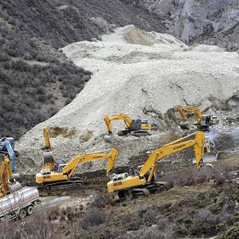 Earthmovers remove rocks and mud from the scene where a landslide hit a mining area in Tibet (AP)