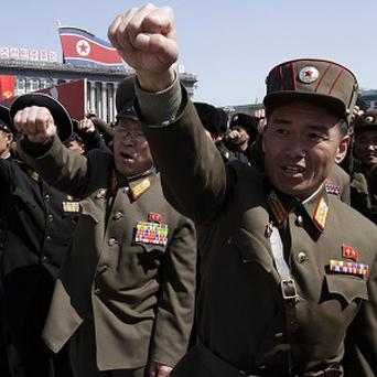 North Korean army officers punch the air as they chant slogans during a rally at Kim Il Sung Square in Pyongyang (AP)