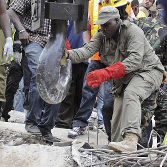 A rescuer guides the hook of a crane as it prepares to remove pieces of rubble from a collapsed building in Tanzania (AP)